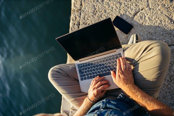 Freiberufler mit Laptop-Netzwerk am Strand