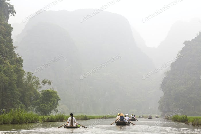 Groups of people in rowboats on a river, mountains in the background.