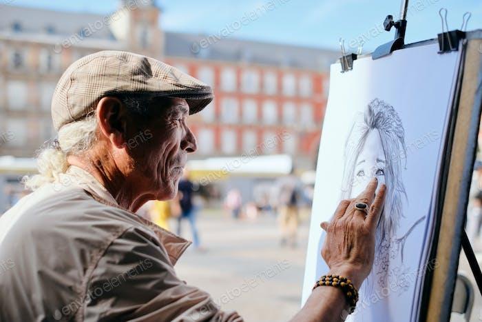 Senior Adult Working As Street Painter In Madrid