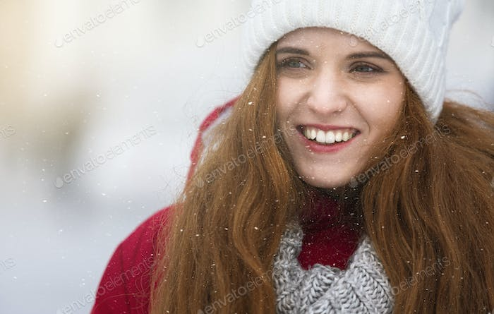 Close up portrait of beautiful ginger girl over snowfall