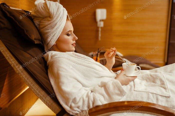Sexy Mädchen entspannen mit Tasse Kaffee im Spa-Stuhl