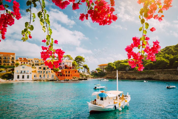 Kefalonia Greece Assos village, fishing boat in tranquil bay and magenta fuchsia blossom