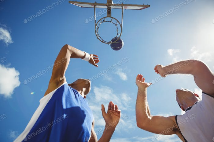Low angle view of friends playing basketball