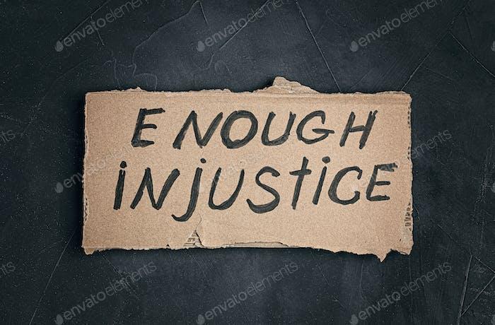 Suficiente texto de injusticia en cartón sobre fondo oscuro