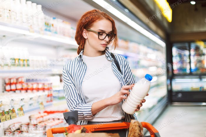 Young woman in eyeglasses and striped shirt with shopping cart t