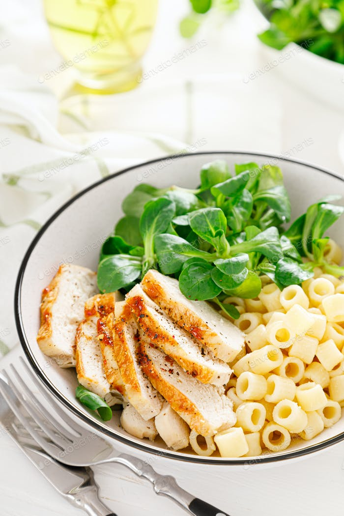 Grilled chicken breast, pasta and fresh lamb salad in lunch bowl