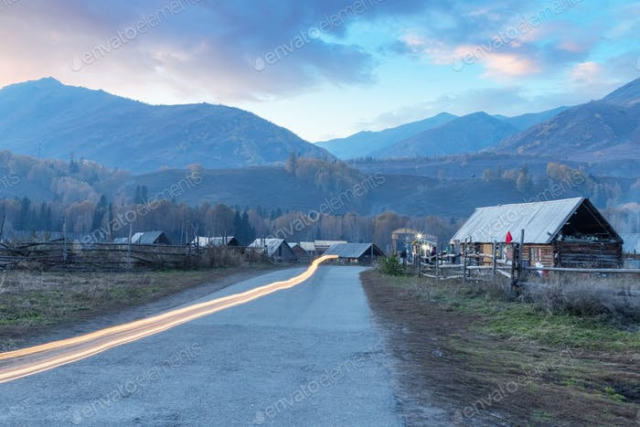 xinjiang hemu village in sunset and light streaks on road from motorbike