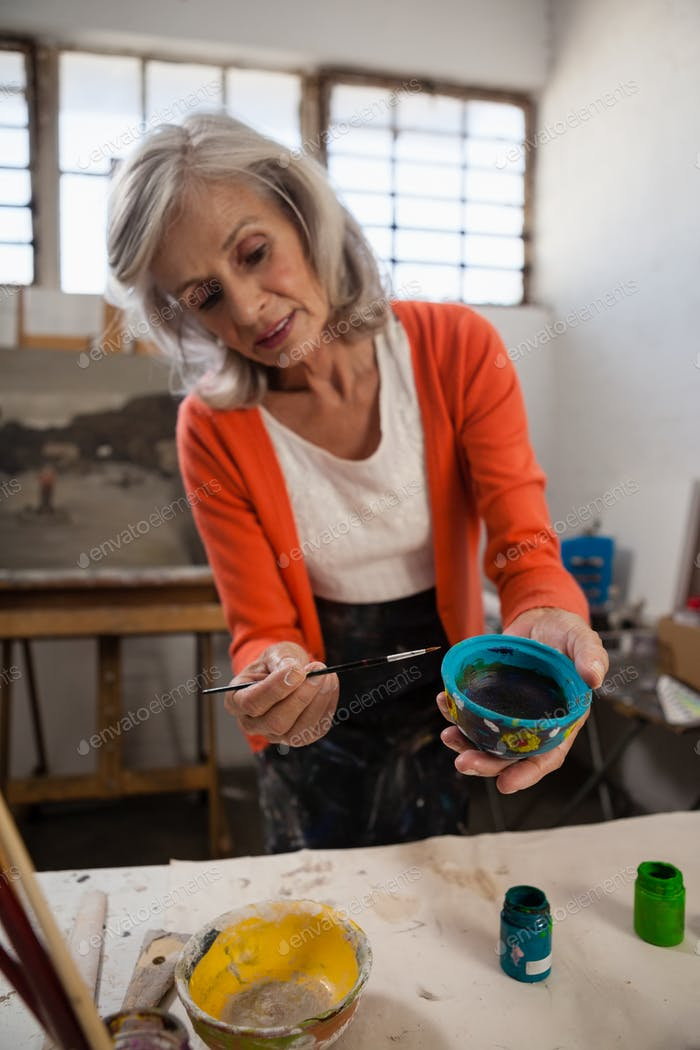 Senior woman painting bowl in drawing class