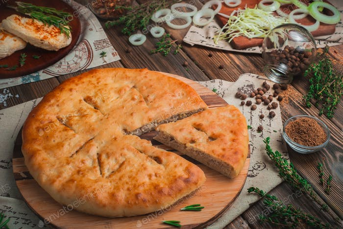Homemade meat pie with chicken, onions, and cabbage. Traditional baking concept, warm colors, wooden