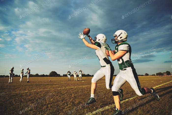 Young American football player making a reception during team practice