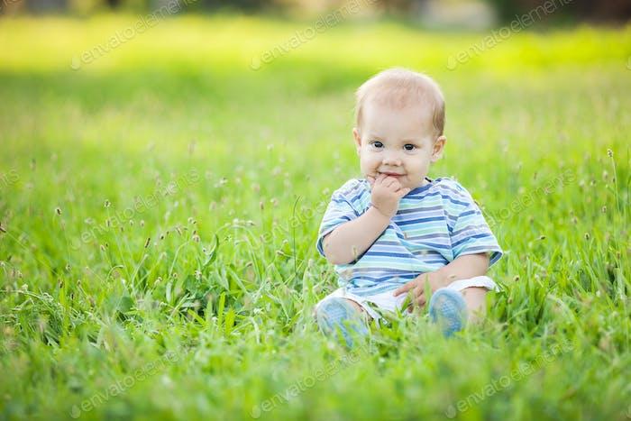 Glücklicher kleiner Junge sitzt auf grünem Gras in einem Park