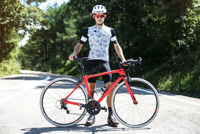 Retrato del joven ciclista con su bicicleta en la carretera.