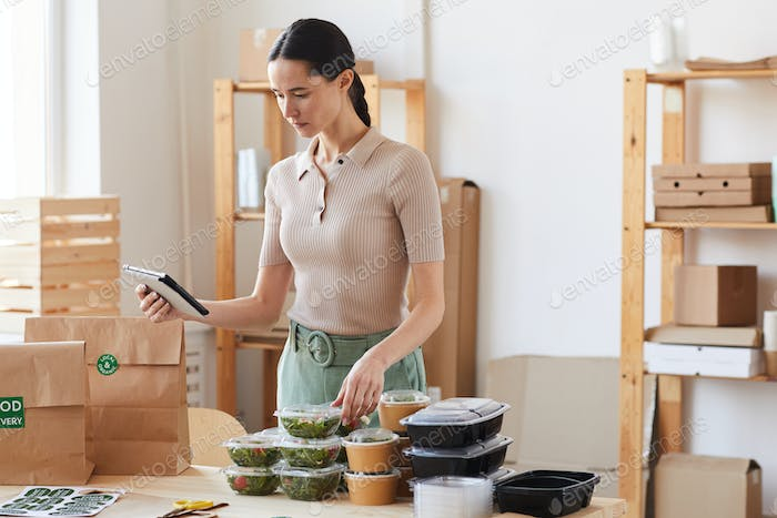 Woman working with online delivery