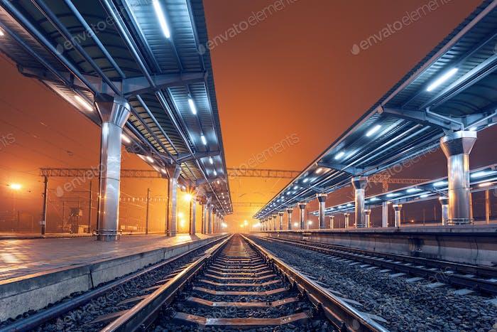 Bahnhof in der Nacht. Bahnsteig im Nebel. Eisenbahn