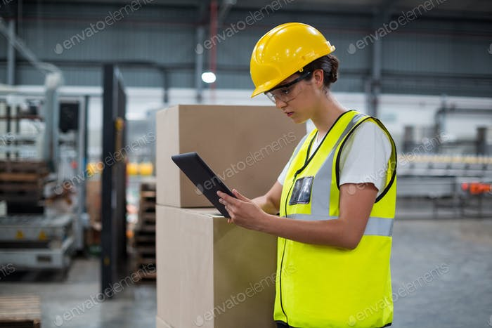 Female factory worker using a digital tablet in factory