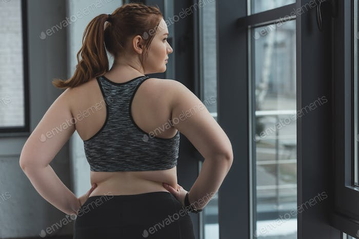 Obese girl wearing sports top in gym