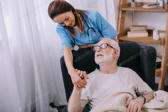 Nurse supporting and holding hand of smiling senior man patient