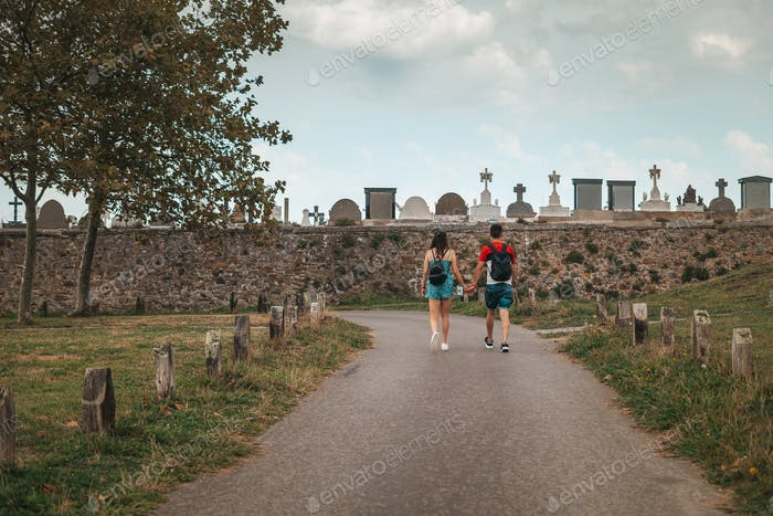 Couple walking by a path near a cemetery in Europe