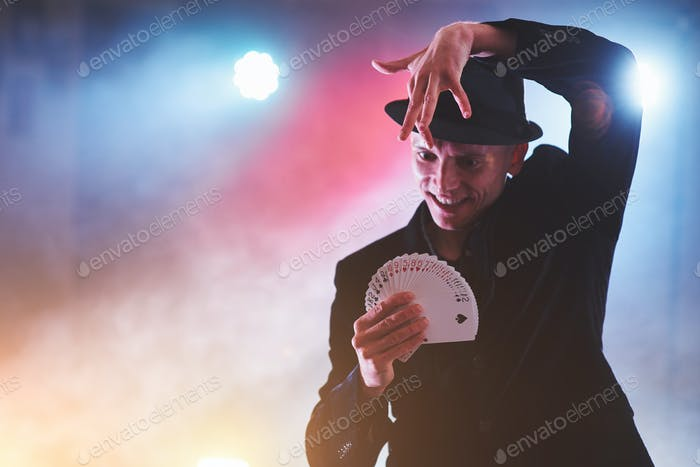 Фокусник показывает трюк с игральными картами. Магия или ловкость, цирк, азартные игры
