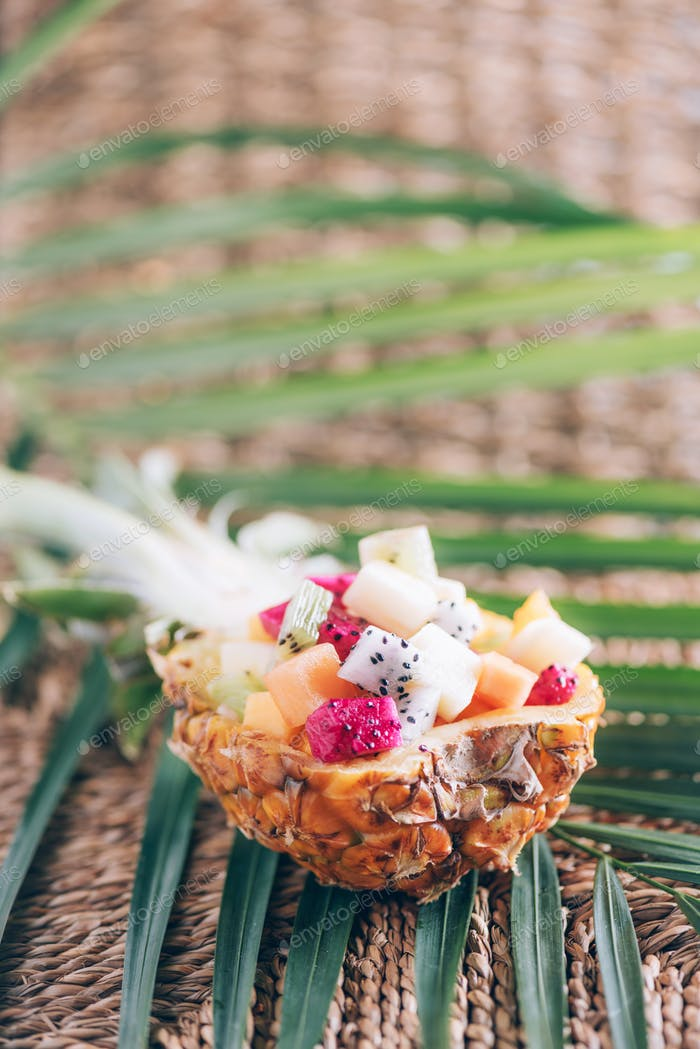 Tropical fruit salad served in half of pineapple fruit over palm leaves on rattan background. Copy