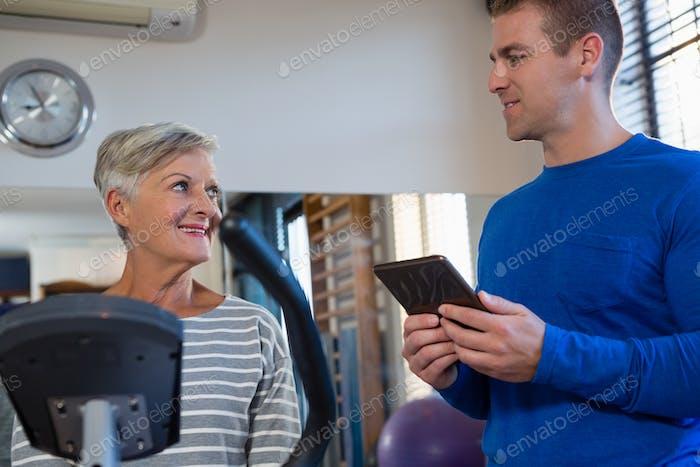 Physiotherapist interacting with senior woman while exercising on exercise bike