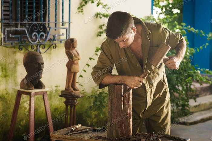 Young Sculptor Artist Working And Sculpting Wood Statue