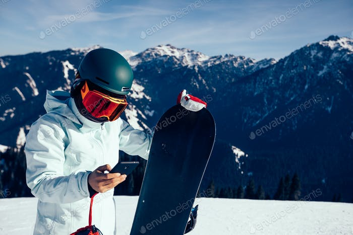 Snowboarder use mobile phone on alpine mountain top