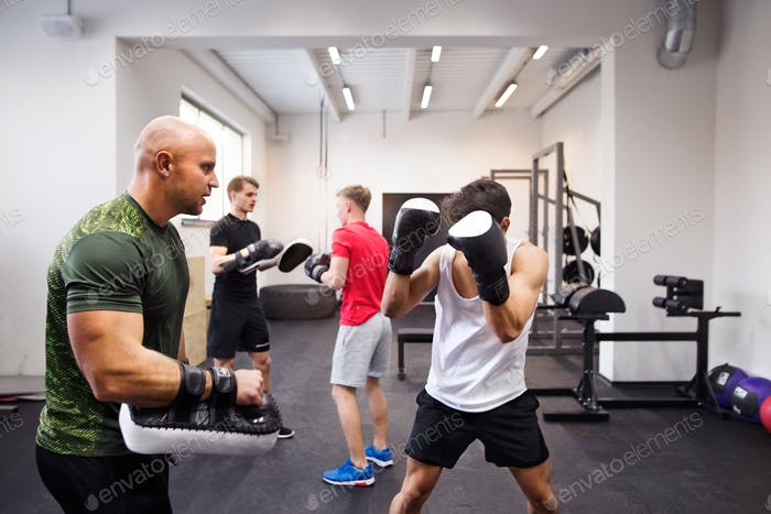 Fit hispanic man in gym boxing with his trainer.