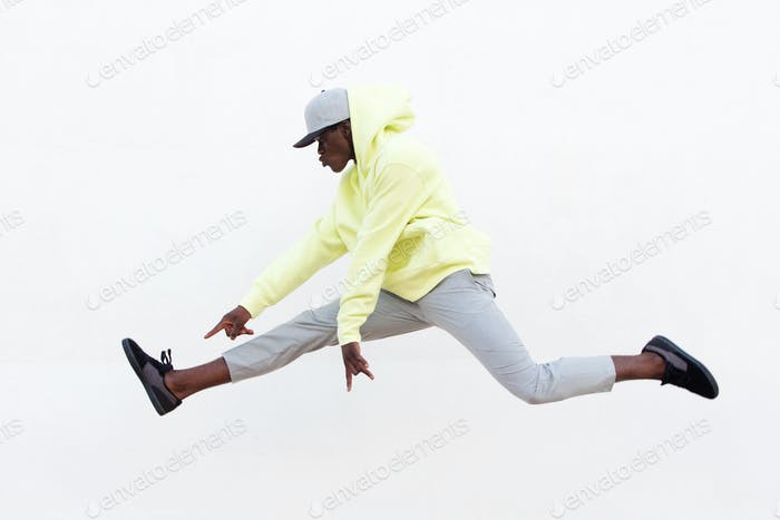 young african man dancer doing leg split in mid air over white background