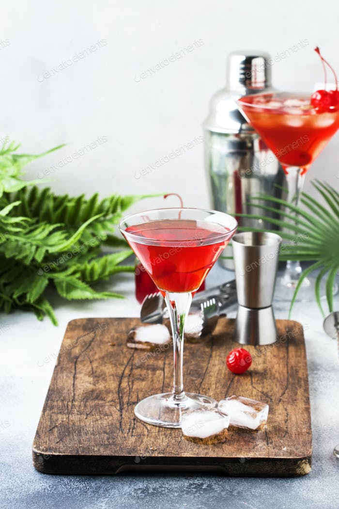 Cosmopolitan cocktail with vodka, liqueur, cranberry juice, lime, ice and orange zest