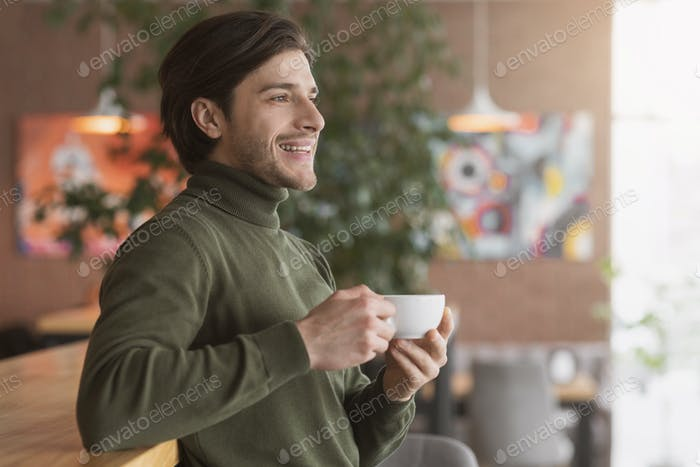 Happy guy drinking tea or coffee at cafe