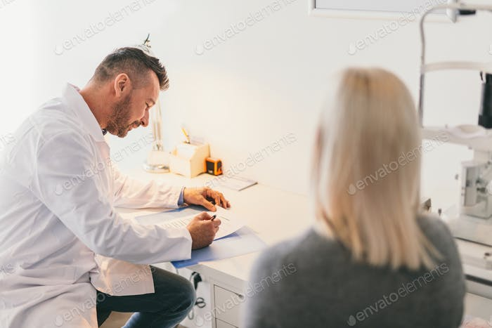 Doctor filling medical questionnaire with a patient.