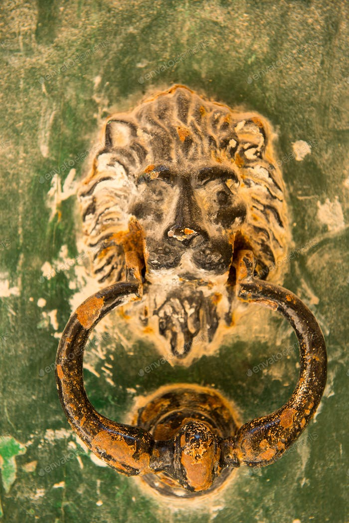 Old rusty lion head knocker in the medieval city of Mdina, Malta