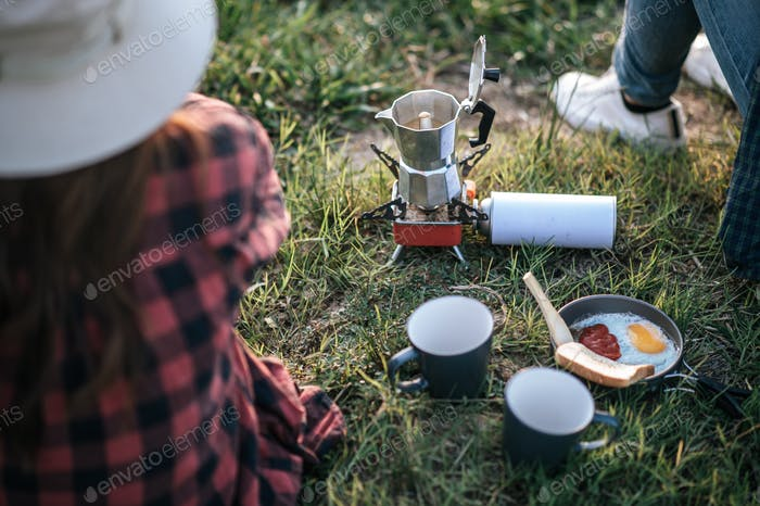 Young Couples camping with morning coffee.