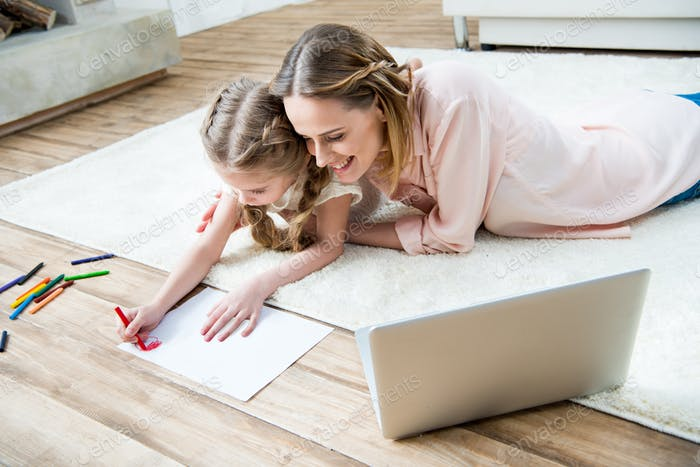 side view of smiling mother looking how concentrated daughter drawing