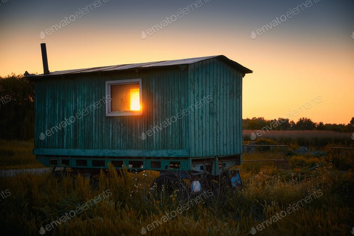 Old caravan on field countryside sunset