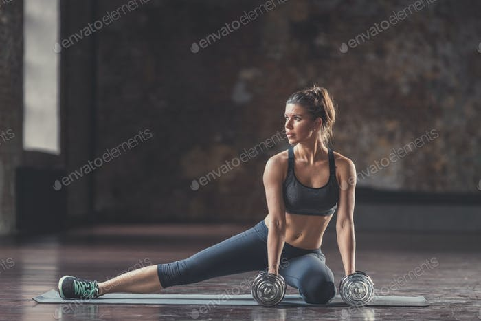 Young athletic girl with dumbbells indoors