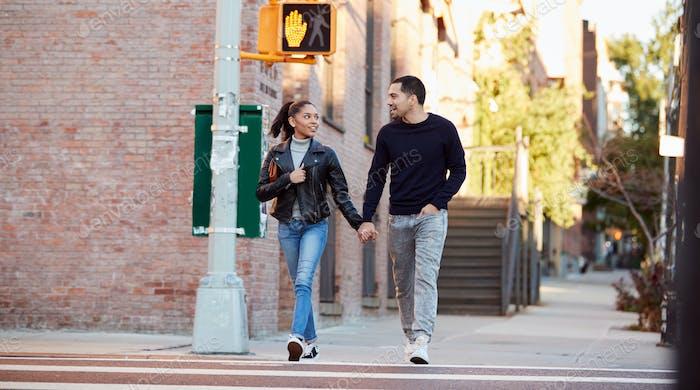 Young Hispanic couple walking hand in hand in Brooklyn