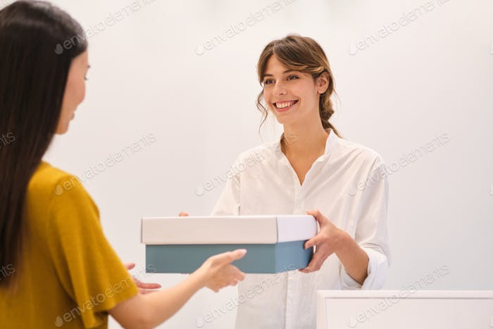 Young pretty positive fashion consultant happily giving shoes in box to client in store