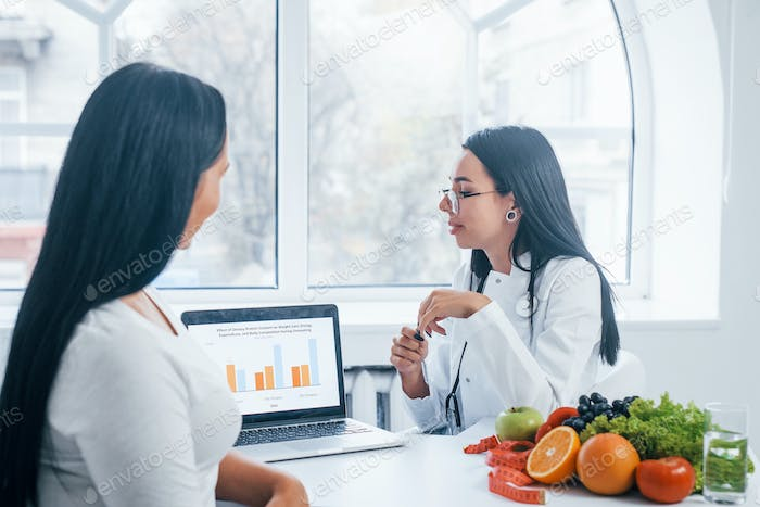 Female nutritionist with laptop gives consultation to patient indoors in the office