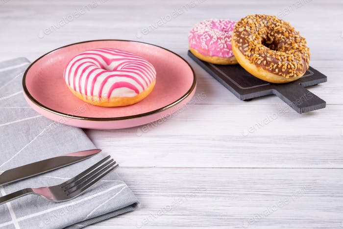 Three donuts on a pink ceramic plate and slate board.