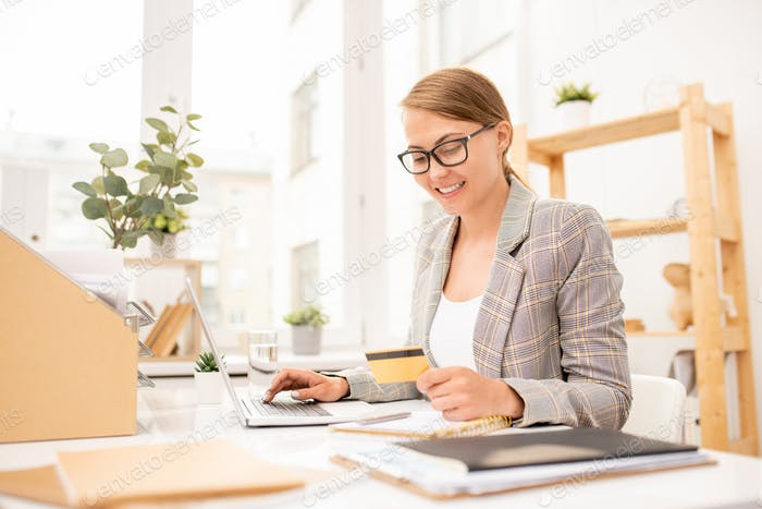Pretty young office worker looking at credit card while making online order