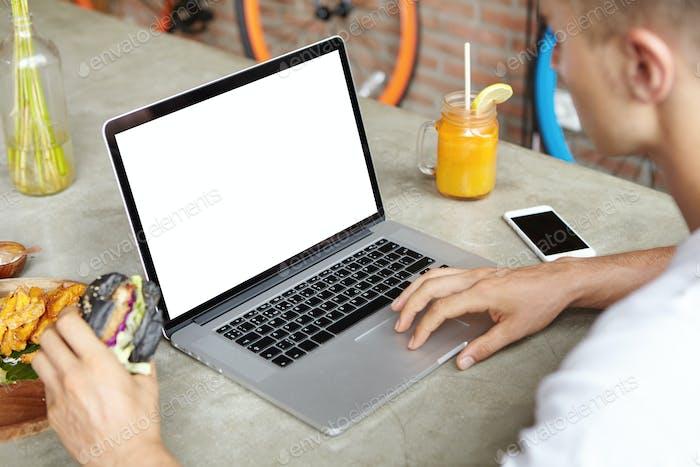 Menschen, Freizeit und Technologie. Blonde Studentin nutzt Wi-Fi auf Laptop und surft im Internet