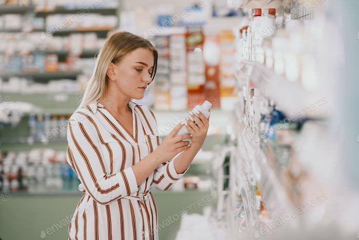 Woman checking medicine in pharmacy