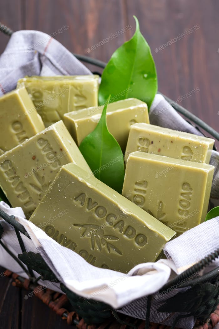 Bars of green natural olive oil soaps with green leaves in a basket on dark wooden background