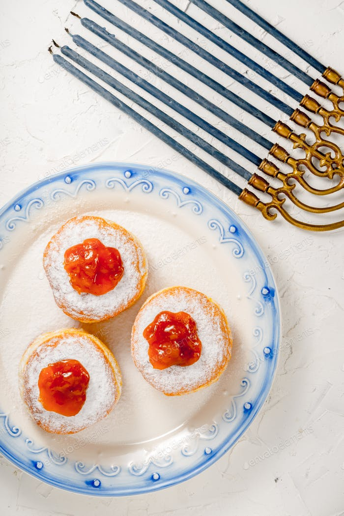 Donuts with jam on a plate with a blue rim and Hanukkah