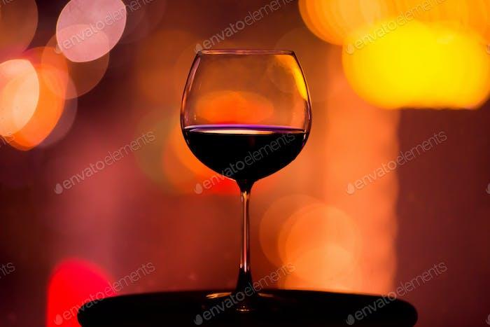 Silhouette von Glas mit Wein. Nachtlicht im Hintergrund.