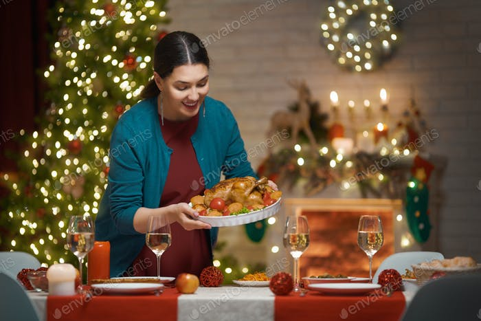 Woman is holding Christmas turkey.