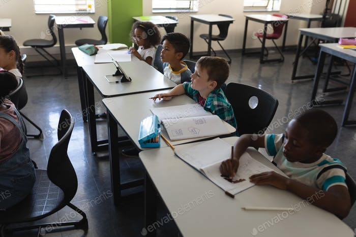 Side view of schoolkids studying and sitting at desk in classroom of elementary school