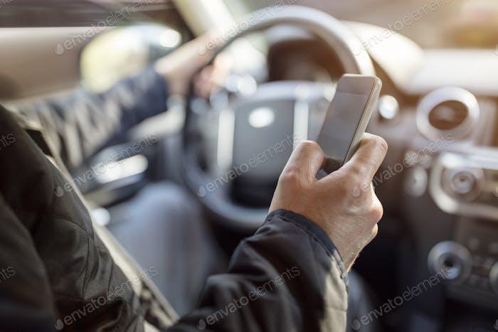 SMS während der Fahrt mit dem Handy im Auto